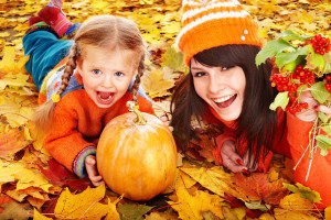 Mom and Child Laying On Leaves with Pumpkin