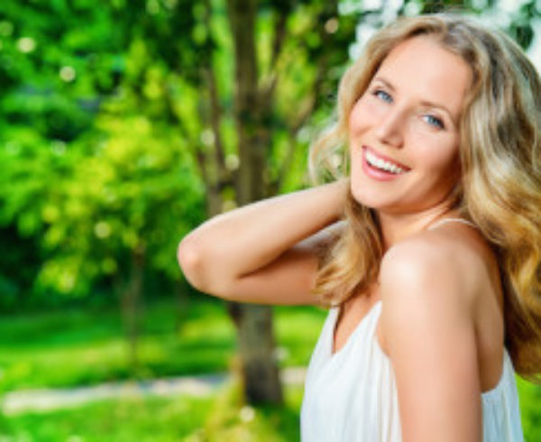 Blonde woman smiling at you outside