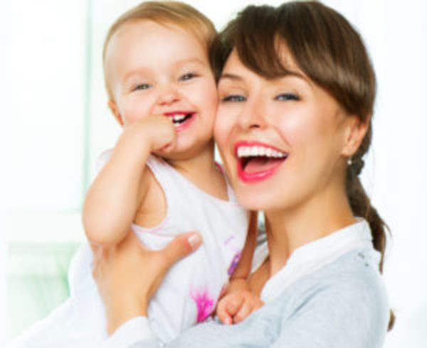 Mother holding baby both laughing with white smiles
