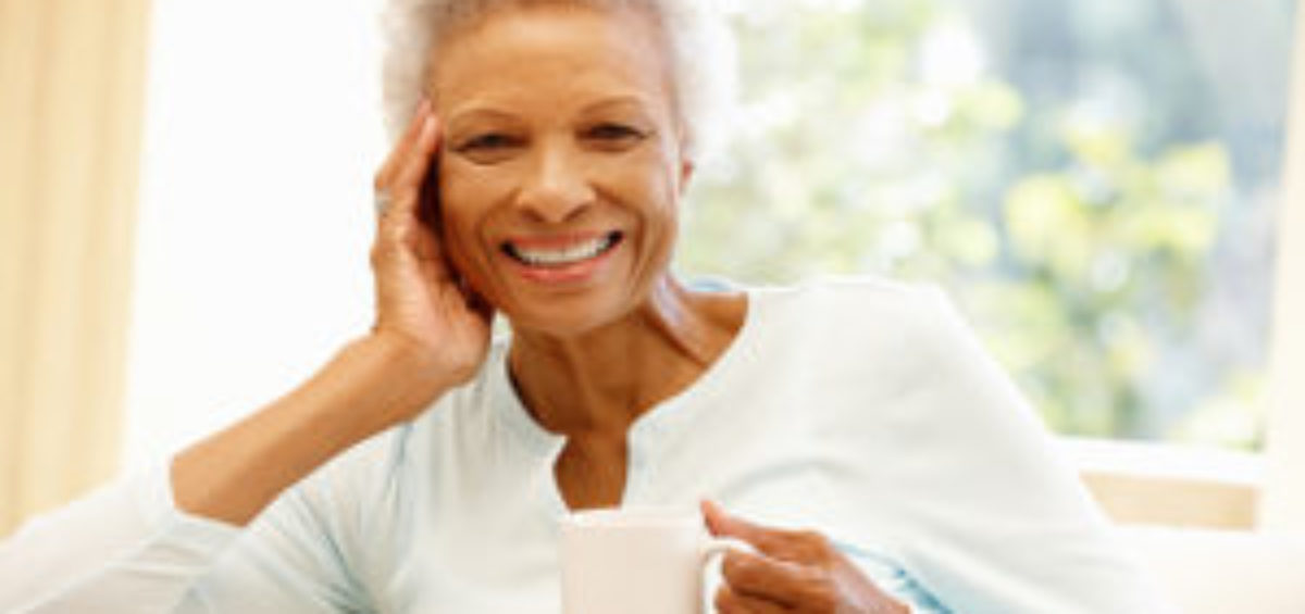 Senior African American woman on couch holding a cup of coffee