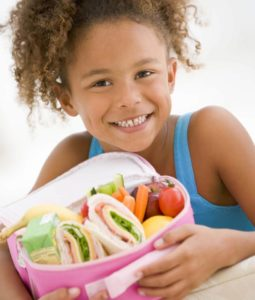 Girl holding lunch box full of healthy foods