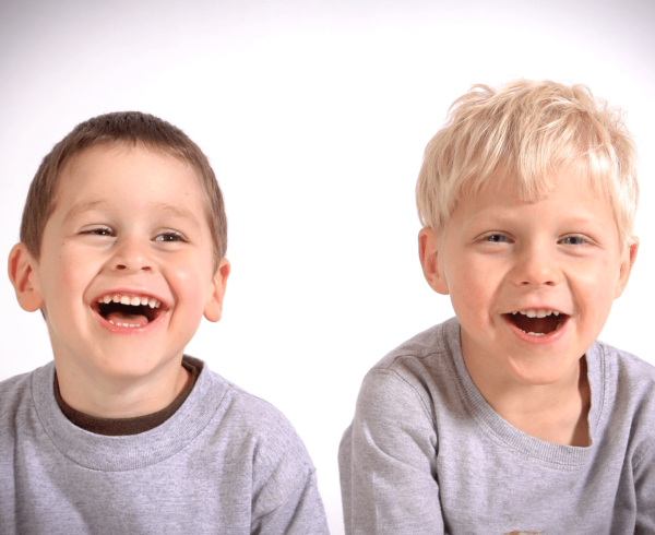 Two young boys laughing at camera