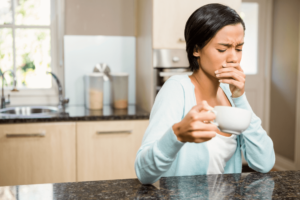 Woman with coffee holding her mouth in discomfort